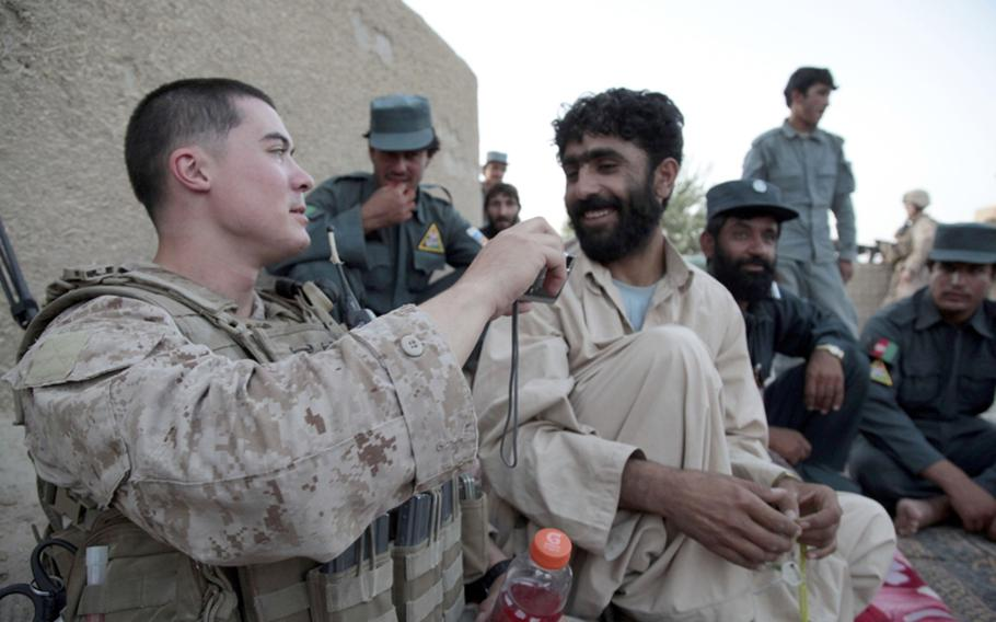 Marine Lance Cpl. Daniel Triebell, a 21-year-old squad leader from Melbourne, Fla., talks with Abdul Baki, second in command at Lakari precinct, about a photo of a low-level Taliban member the police caught wearing women's clothing. Triebell is a member of Company A, 1st Battalion, 3rd Marine Regiment.