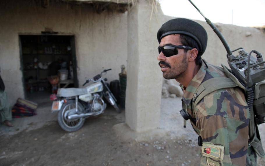 Wazir, an Afghan soldier, awaits his change after buying a pack of cigarettes during a joint patrol with U.S. Marines on July 21.