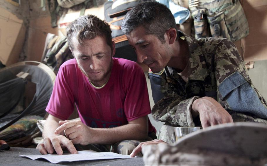 Afghan squad leader and Army Sgt. Amrullah, left, a teaches Sgt. Yahmatullah, another squad leader, how to read a map during a visit to Amrullah's patrol base.