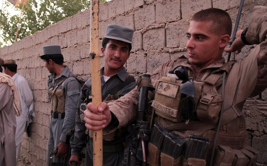"""Marine Sgt. Michael Cucinotta, a 25-year-old squad leader from Rochester, N.Y., horses around with an Afghan Uniformed Police patrolman during a patrol July 25. Cucinotta said the Marines and patrolmen at Checkpoint 4, where they are stationed, get along well, and that the Afghans are willing and able to conduct patrols. Cucinotta, a member of Weapons Company, 1st Battalion, 3rd Marine Regiment, calls the six policemen assigned to his checkpoint """"The All-Stars,"""" because of their willingness to patrol and take the lead."""