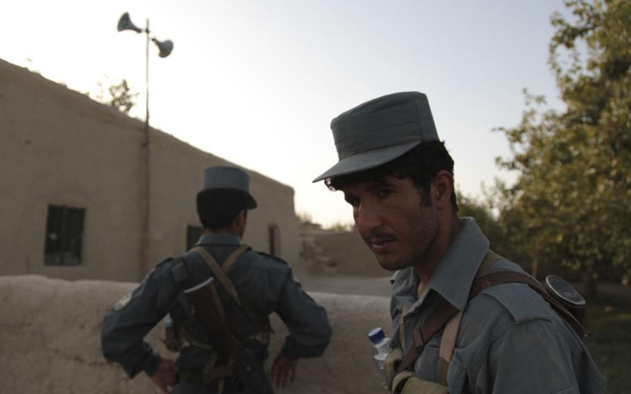 Afghan Uniformed Police patrolmen stop by a mosque for evening prayer during a patrol through villages near Patrol Base Gorgak in the middle of Helmand province's Garmsir district.