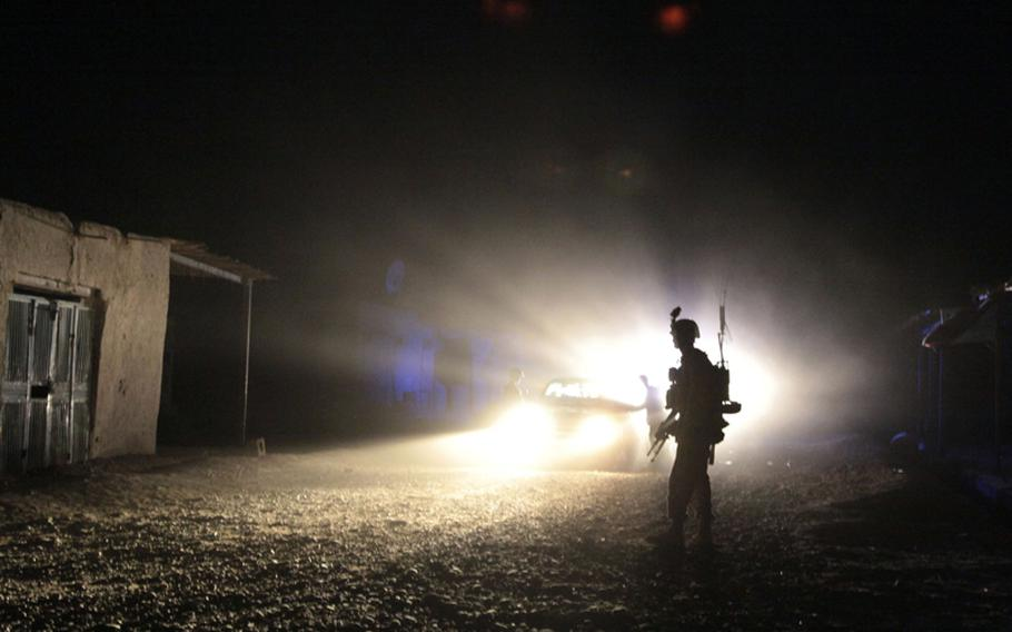 A Marine of Company C, 1st Battalion, 3rd Marine Regiment, patrols the Safar Bazaar after dark July 28. Marines had jumped to get ready after an alert was issued on a suspicious car, then had to wait for more than half an hour as their Afghan counterparts got ready for what was supposed to be a quick-reaction force mission.
