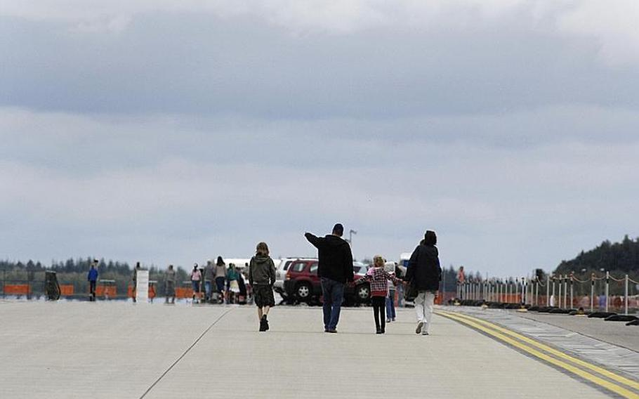 A family walks toward the viewing area to watch the aerial demonstrations during the Spangdahlem Air Base open house on Saturday, July 30, 2011.