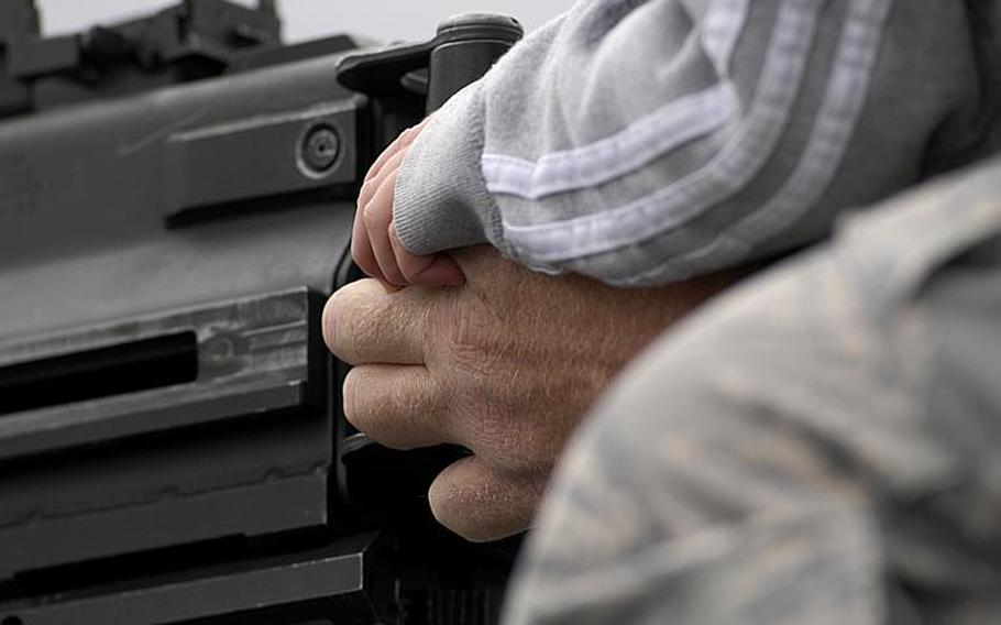 A young boy grips the hand of Staff Sgt. Bruce Rick, with the 52nd Security Forces Squadron, as Rick shows base visitors a MK-19 grenade launcher mounted on a Humvee during the Spangdahlem Air Base open house on Saturday, July 30, 2011.