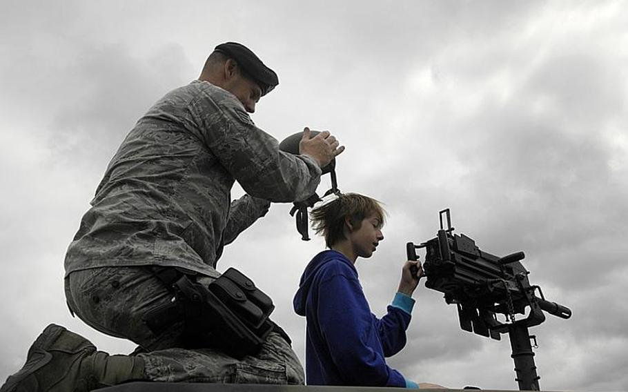 Staff Sgt. Bruce Rick, with the 52nd Security Forces Squadron, takes a helmet off a young boy as the boy checks out an MK-19 grenade launcher mounted on a Humvee during the Spangdahlem Air Base open house on Saturday, July 30, 2011.