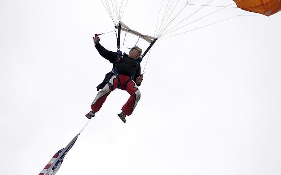 A member of the Firebirds parachute demonstration team displays the U.S. flag as he performs Saturday, July 30, 2011, at the Spangdahlem Air Base, Germany, open house and aerial demonstration. Team members are civilians from Bitburg, Germany.