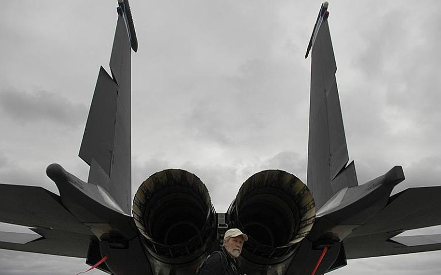 A spectator passes by the tail end of an F-15E Strike Eagle during the Spangdahlem Air Base open house and aerial demonstration on Saturday, July 30, 2011.