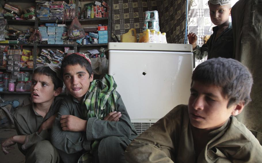 Mohammed Nabi, left, was at his father's store when two men shot and stabbed two Afghan soldiers at the shop next door. Nabi, 10, fled the store after he heard gunshots. Later, Afghan troops rampaged through his father's shop, shooting up his merchandise and his freezer, where there is still a hole.