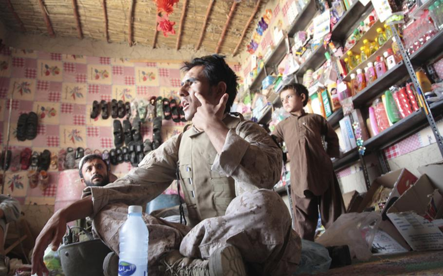Qahar Farzan, an interpreter from Kabul who works with U.S. Marines in southern Garmsir district, Helmand province, translates during an interview with Yar Mohammed, a shopkeeper whose store was ransacked in June by Afghan troops after two of their men were shot nearby.