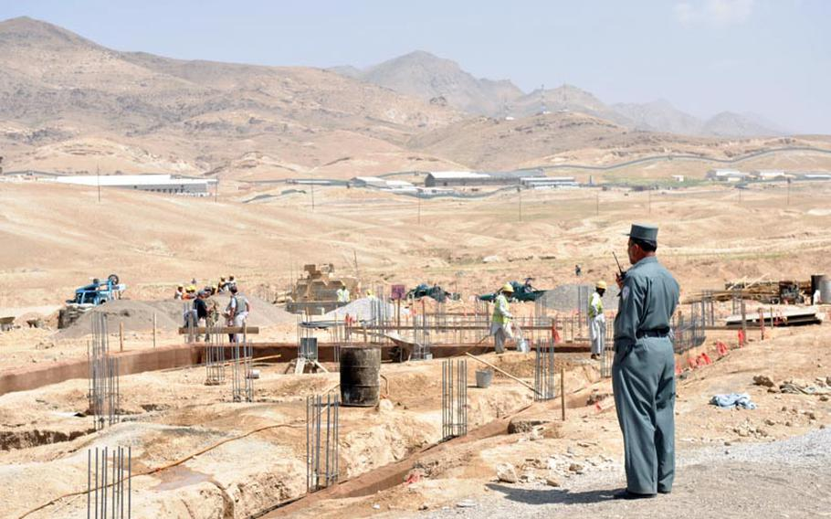 An Afghan policeman stands guard at the construction site of a new prison in Maidan Shar, capital of Wardak province.