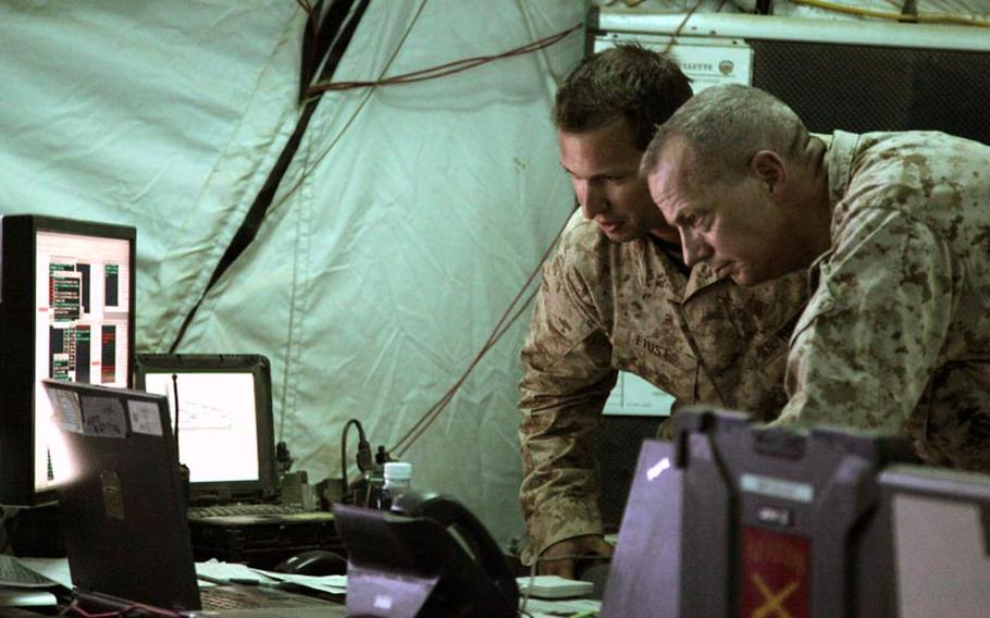 Gen. John R. Allen, right, commander of the International Security Assistance Force and U.S. Forces - Afghanistan, gets a short brief during a battlefield circulation Thursday.