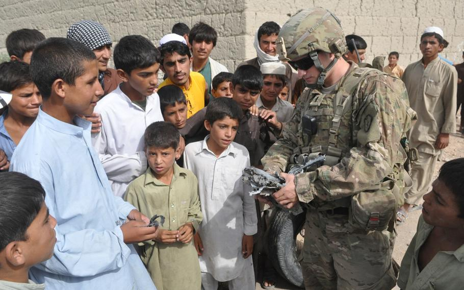 Onlookers crowd around 1st Lt. Mark Ziegenfuss last week as he examined a piece of debris after U.S. soldiers removed an IED from a dirt road in Rodat, a village in eastern Nangarhar province.