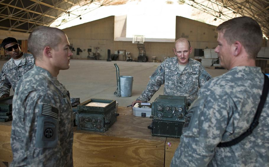 Sgt. William Carlisle, second from right, of St. Augustine, Fla., processes broken laptops, printers and GPS systems on Aug. 15, 2011, that were turned in at the Redistribution Property Assistance Team yard at Al Asad Air Base in Al Anbar province, Iraq. As U.S. forces draw down, Carlisle helps facilitate the collection and shipping of goods here that are leaving Iraq.