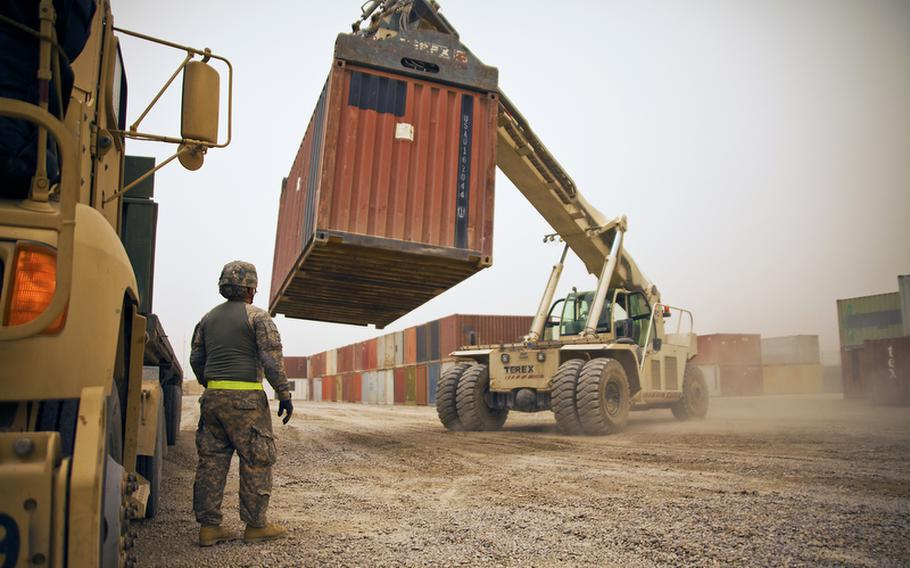 Pfc. Jesus Valladares, from the 68th Transportation Company, 142nd Combat Sustainment Support Battalion oversees the loading of a cargo truck at the U.S. Army's largest Central Receiving and Shipping Point yard at Sather Air Base outside Baghdad. The containers are full of goods that have arrived from closing bases throughout Iraq and are headed to Contingency Operating Base Adder, an enduring U.S. base in Tallil, Iraq.