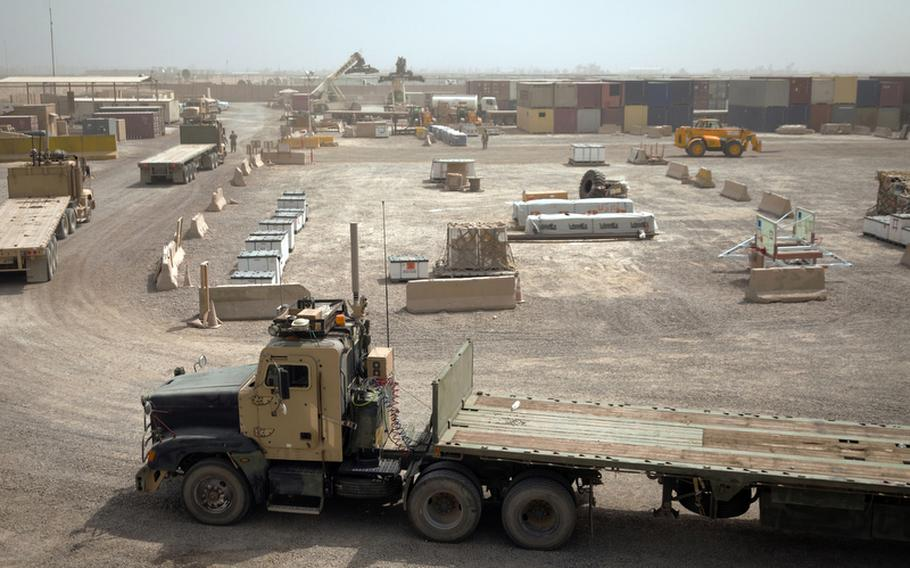 Armored cargo trucks prepare to load cargo at the largest U.S. Army Central Shipping and Receiving Point yard in Iraq at Sather Air Base outside Baghdad on Aug. 18, 2011. Trucks will be loaded with goods brought to Sather from bases that are drawing down and closing and transported to Contingency Operating Base Adder, an enduring U.S. base in Tallil, Iraq.