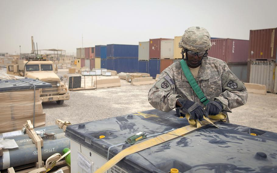 Sgt. Walter Washington, of Eastern Shore, Md., with the 68th Transportation Company, 142nd Combat Sustainment Support Battalion, cinches down cargo that came from closing bases throughout Iraq at Sather Air Base's Central Receiving and Shipping Point yard. The items are headed to Contingency Operating Base Adder, a U.S. Base in Tallil, Iraq, to support the enduring operation there.