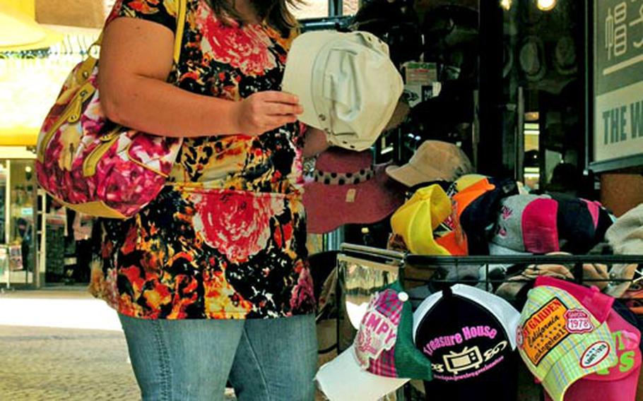 Army spouse Jennifer Rodriguez browses the hats at American Village. The shopping and entertainment complex was once U.S. Army land but now is one of the biggest commercial draws in central Okinawa. The island hopes it can repeat that success when other military land is returned in the future.
