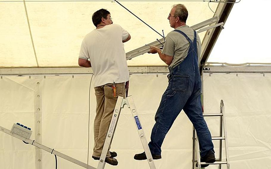 Markus Hunsinger (left) and Ferdinand Eisenzimmer, electricians with ITT Federal Services, install lighting inside the temporary tent that will serve as the shoppette on Kleber Kaserne after a fire destroyed the Kleber shoppette late Sunday night.  Joshua L. DeMotts/Stars and Stripes