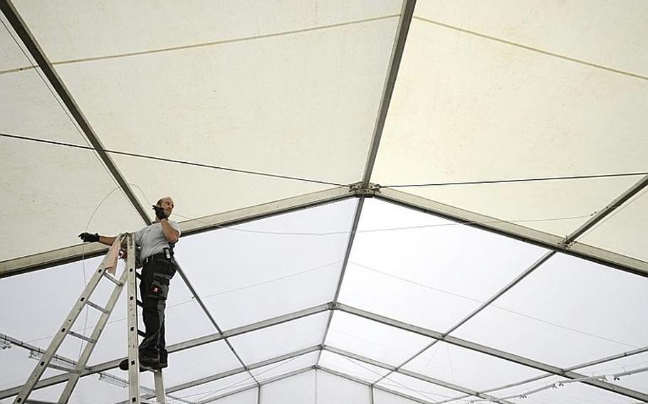 Erik Schwehm, an electrician with ITT Federal Services, installs lighting inside the tent that will serve as the shoppette on Kleber Kaserne after a fire destroyed the Kleber shoppette late Sunday night.