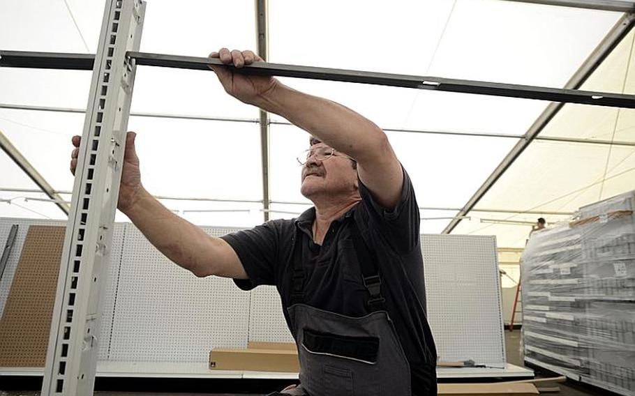 Mike Kullmer, an AAFES mechanic, assembles shelving inside the tent that will serve as the shoppette on Kleber Kaserne after a fire destroyed the Kleber shoppette late Sunday night.