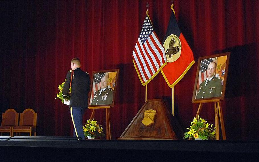 A soldier walks past the portrait of Sgt. Matthew Harmon following Wednesday's memorial ceremony for Harmon and Spc. Joseph VanDreumel, pictured at right. Harmon and VanDreumel, mechanics with Company A, 1st Battalion, 2nd Regiment, Task Force 3-66, were killed by a roadside explosion on Aug. 14 in eastern Afghanistan.