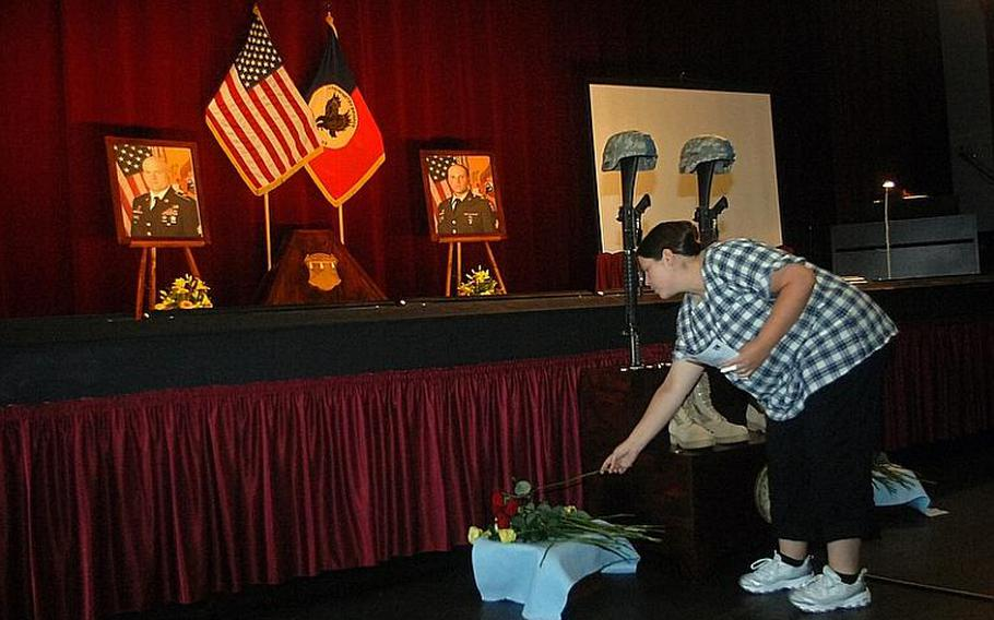 An attendee lays a flower before a memorial to Sgt. Matthew Harmon and Spc. Joseph VanDreumel, two mechanics with the 172nd Separate Infantry Brigade killed in Afghanistan by a roadside explosion on Aug. 14.