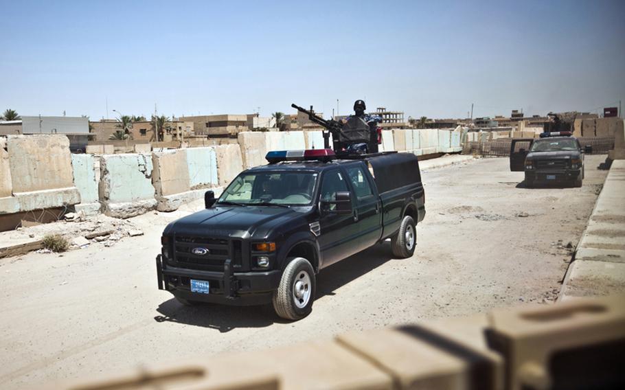 Iraqi Police in trucks, modified Ford F-350 pickups, guard the entrance to Ramadi Police Headquarters on Aug. 13 in Ramadi, Iraq.