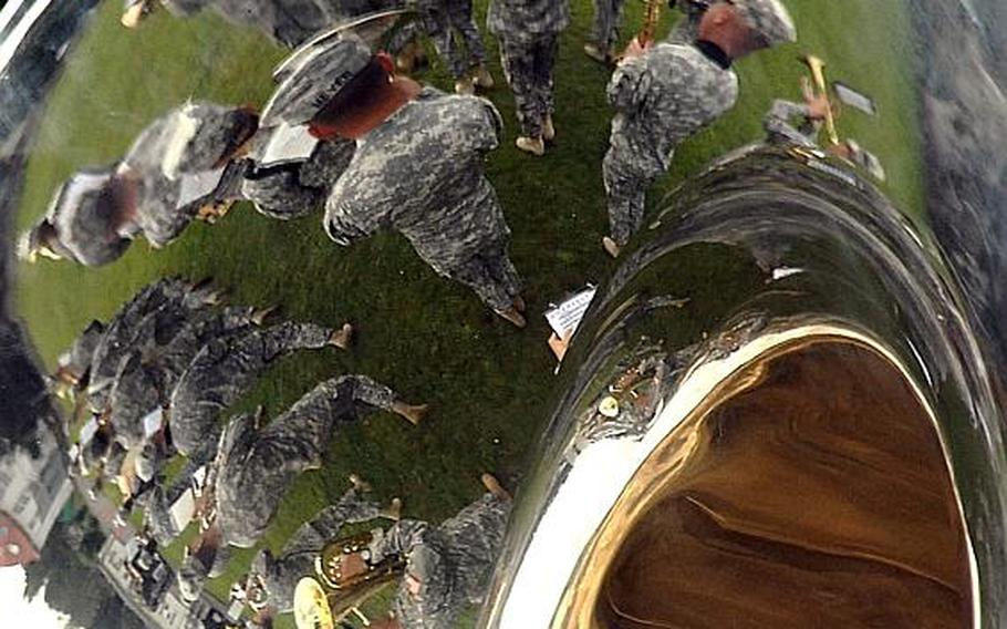 Members of the United States Army Europe Band are reflected in a tuba as they march at the beginning of the the 21st Theater Sustainment Command's change of command ceremony at Daenner Kaserne in Kaiserslautern, Germany, on Thursday. Brig. Gen. Aundre Piggee took over the reins of the 21st TSC from Maj. Gen.Patricia McQuistion who is to be the commanding general of the U.S. Army Sustainment Command in Rock Island, Ill.