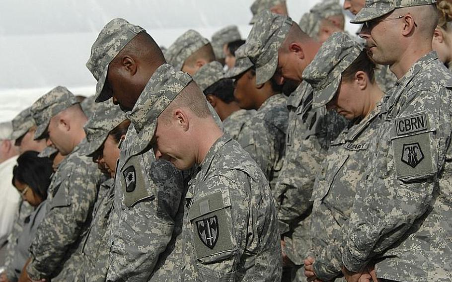 Soldiers pray during the 21st Theater Sustainment Command's change of command ceremony at Daenner Kaserne in Kaiserslautern, Germany, on Thursday. Brig. Gen. Aundre Piggee took over the reins of the 21st TSC from Maj. Gen.Patricia McQuistion who is to be the commanding general of the U.S. Army Sustainment Command in Rock Island, Ill.