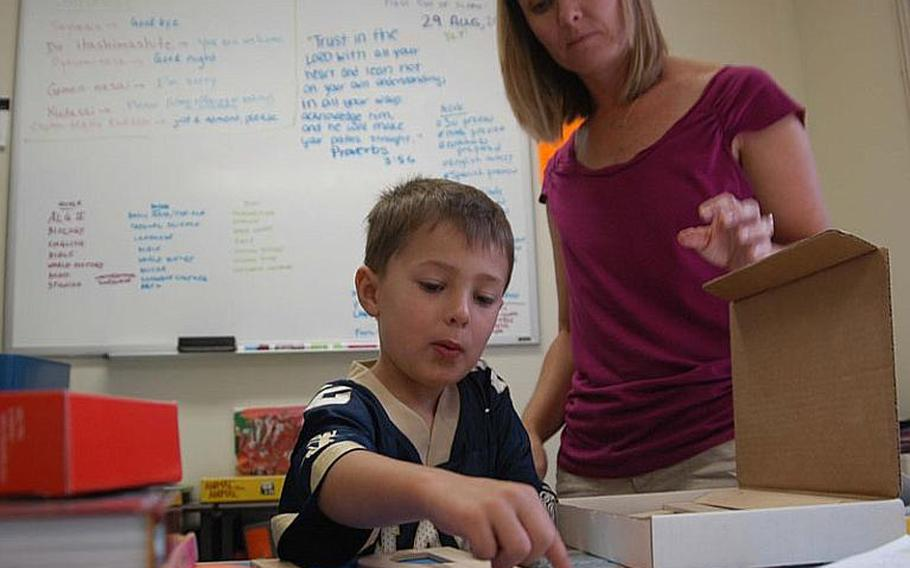 Kathy Stevens  looks over the shoulder of her 4-year-old son Will, a homeschooled preschooler, as he practices handwriting using manipulatives Friday at the family home. Homeschoolers are a small but growing population amongst American children. Military families said that there are even more benefits to homeschooling amongst their community.