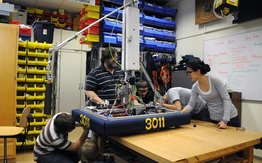 Last February Wiesbaden robotics club adviser Frank Pendzich, center, watched as Tim Kanser, Riley Pickering, Kenny Philips, Dhillon Tisdale and Shena Cousens, from left, attached skirting to the RoboWarriors' robot as they got it ready to be shipped off to Las Vegas for the  FIRST Robotics Competition. DODEA is launching a pilot program at a handful of DODEA schools this year focusing on the STEM (science, technology, engineering and math) initiatives, and robotics engineering is one of the classes.