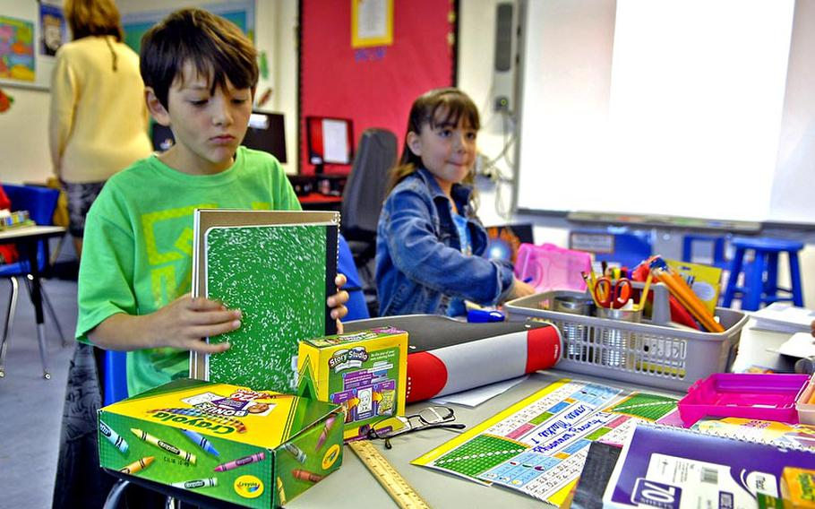 Conner Mackie, 9, organizes his school supplies on the first day of the new school year Monday in Laura Rahaim's fourth-grade class at Vogelweh Elementary School in Kaiserslautern, Germany.