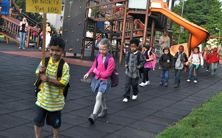 First-grader Elezar Martinez leads his classmates into Smith Elementary School Monday at U.S. Army Garrison Baumholder in Germany. It was the first day of school for pupils at Department of Defense Dependents Schools-Europe.