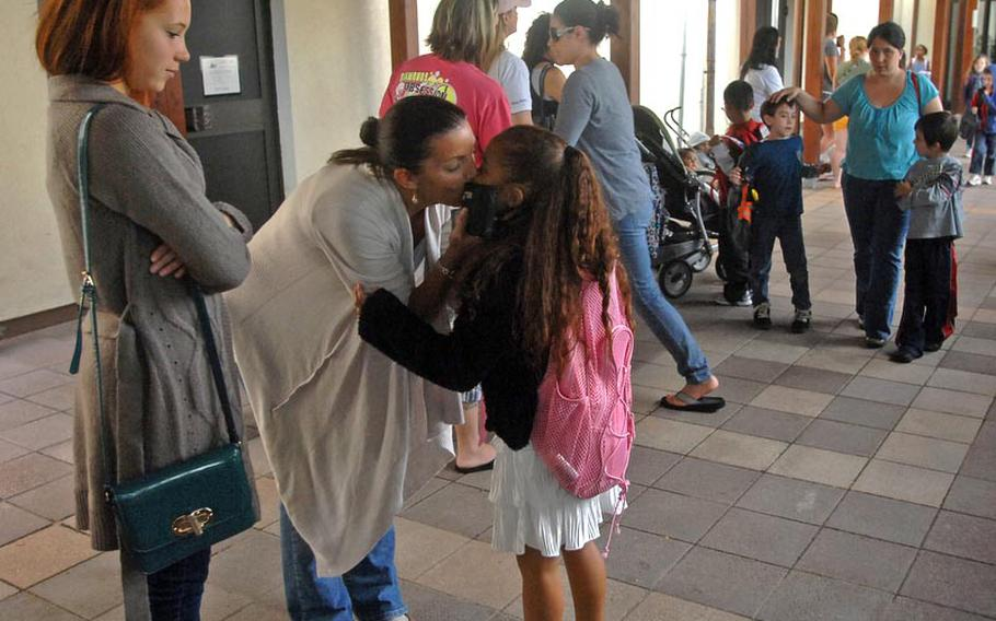 Cheryl Buggs embraces her daughter, Victoria, 7, after Victoria's first day in the second grade at Grafenwoehr Elementary School. The school enrolled roughly 300 children for the school year, principal Crystal Bailey said.
