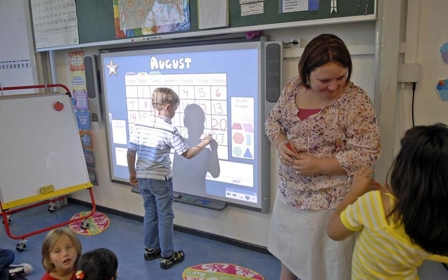 Second-grader Jameson Muse writes a calendar date on a Smart Board, while teacher Holly Magcalas helps another student on the first day of school Monday at Vogelweh Elementary School in Kaiserslautern, Germany.