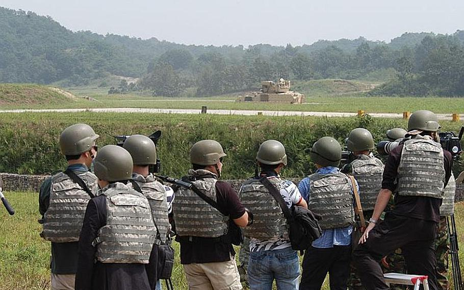 Media representatives look on as an M2A3 Bradley Infantry Fighting Vehicle is put through its paces at an exercise Sept. 1, 2001, near the Demilitarized Zone. More than 100 media members were on hand for the demonstration of new equipment recently brought to South Korea by the U.S. military.