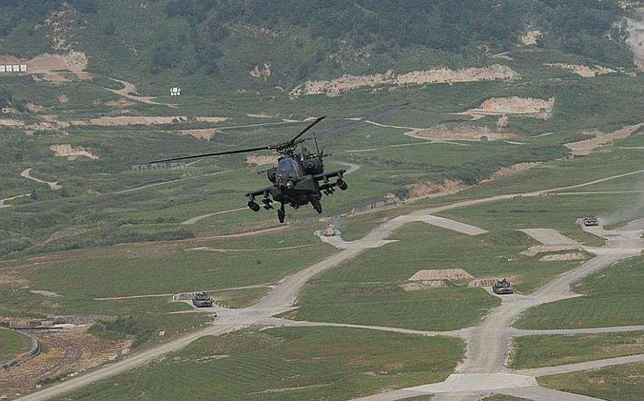 """An AH-64D Apache Longbow flies back after firing its weapons during a joint U.S.-South Korean military exercise Sept. 1, 2011, south of the Demilitarized Zone, as the tanks and fighting vehicles below continue the """"fight.""""."""