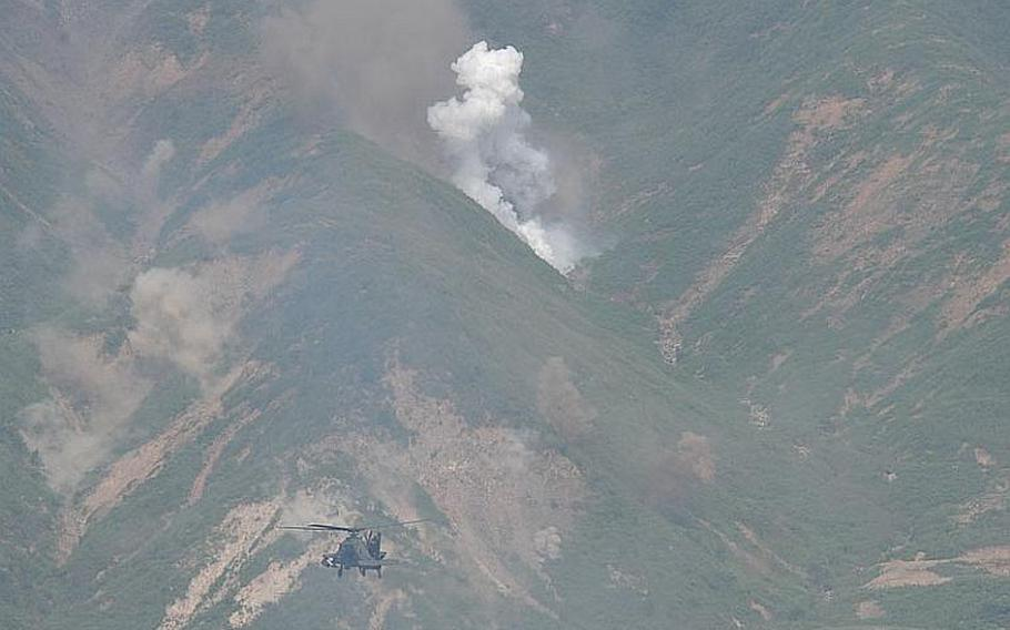Smokes rises from a mountainside as an AH-64D Apache Longbow helicopter fires on a target during a joint U.S.-South Korean military exercise Sept. 1, 2011, near the Demilitarized Zone.