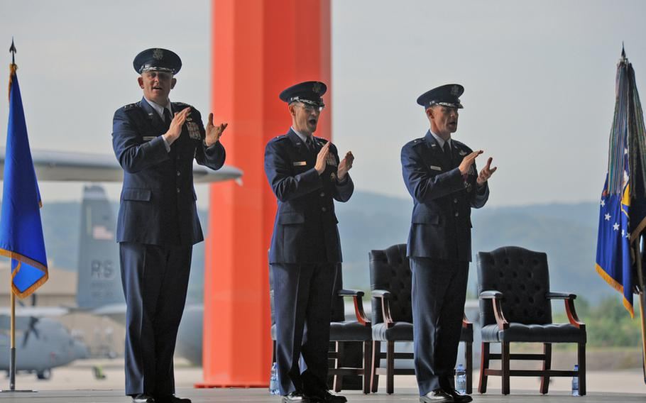 Third Air Force Commander Lt. Gen. Frank Gorenc, the new 86th Airlift Wing commander Brig. Gen. Charles Hyde and the wing's former commander Brig. Gen. Mark Dillon, from left, clap along as they sing the Air Force Song at the wing's change of command ceremony at Ramstein Air Base, Germany, on Friday. The 86th AW is the largest wing in the U.S. Air Forces in Europe.