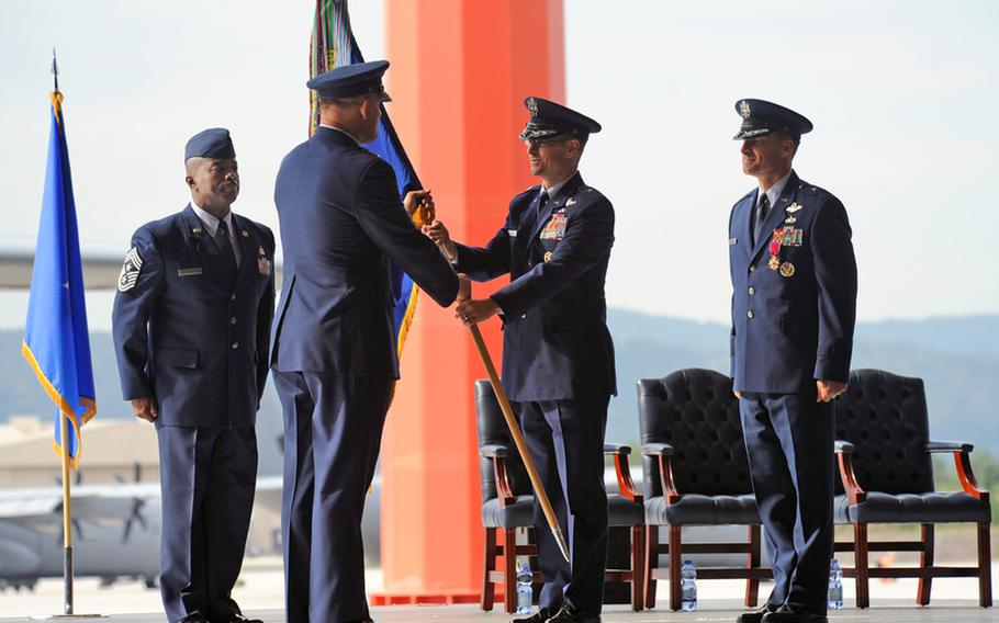 At a ceremony at Ramstein Air Base, Germany, on Friday, incoming commander Brig. Gen. Charles Hyde takes the 86th Airlift Wing colors from Lt. Gen. Frank Gorenc, commander 3rd Air Force, as the wing's outgoing commander Brig. Gen. Mark Dillon watches at right. At left is Command Chief Master Sgt. Zef Smith.