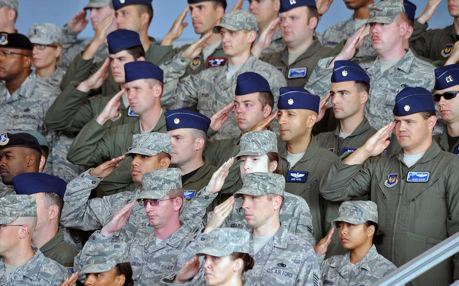 Airmen of the 86th Airlift Wing salute during the singing of the national anthems at the wing's change of command ceremony at Ramstein Air Base, Germany, on Friday. Brig. Gen. Charles Hyde took command of the wing from Brig. Gen. Mark Dillon.
