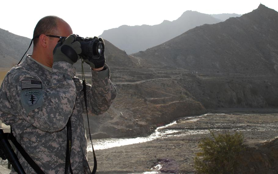 Army Master Sgt. Martin Cervantez takes pictures of soldiers on a mission during an embed in Afghanistan. Cervantez and Marine Staff Sgt. Kristopher Battles often take photos downrange, then go back to the States and produce paintings based on those impressions.