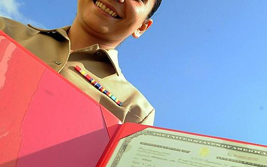 Twenty two year old, Lance Cpl. Sara Zayii, displays her naturalization certificate after the naturalization ceremony at Camp Foster, Friday. She was born in Iraq and came to the United States when she was 11 years old.