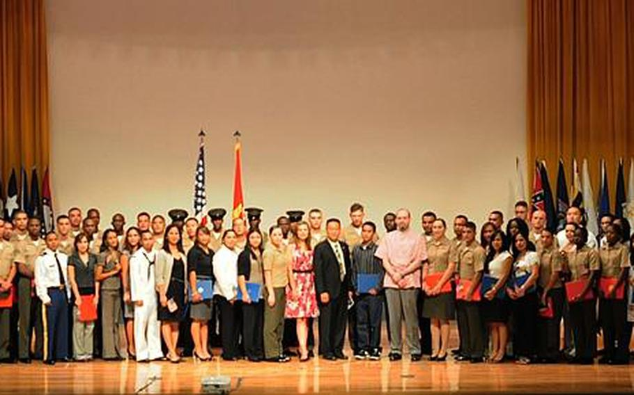 Sixty-seven newly sworn in American citizens stand with guest speakers and honored guests after the conclusion of the naturalization ceremony at Camp Foster base theater Friday morning.