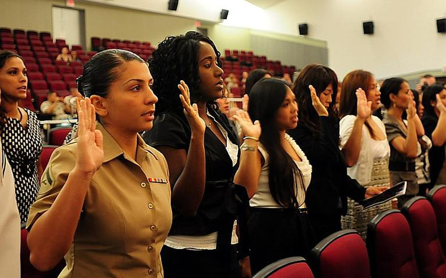 Lance Cpl. Sara Zayii, recites the Pledge of Allegiance during the naturalization ceremony at Camp Foster Friday morning. She was one of 67 service members and spouses that became naturalized American citizens.