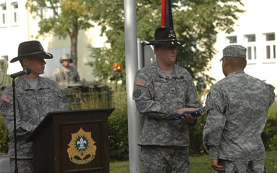 During a Sunday ceremony at Rose Barracks in Vilseck, Col. Keith Barclay, commanding officer of the 2nd Stryker Cavalry Regiment, accepts an American flag that accompanied a steel I-beam from the World Trade Center. The artifact was to be transported to nearby Oberviechtach for a German 9/11 memorial.