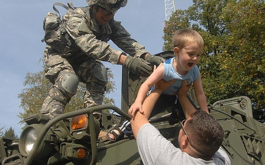 A soldier with the 2nd Stryker Cavalry Regiment hoists 4-year-old Wyatt Moore from the top of a Stryker down to the arms of his father, Sgt. Matthew Moore, 33, of the Regimental Support Squadron before Sunday's 9/11 memorial ceremony at Rose Barracks in Vilseck.