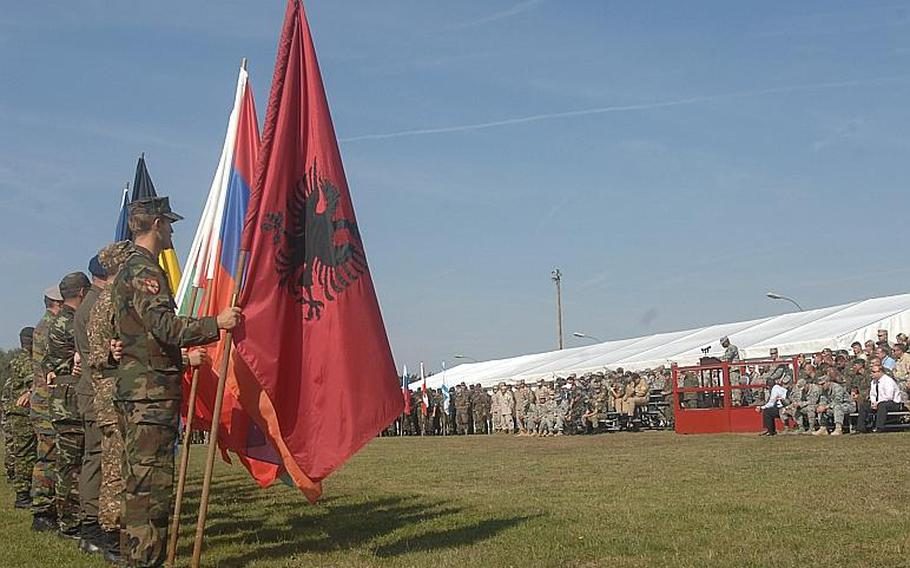 Soldiers from 18 countries that lost citizens in the 9/11 attacks on the World Trade Center and the Pentagon hold the flags of their respective nations during a European Command ceremony on Sunday at the Grafenwoehr Training Area. EUCOM is holding a multinational training exercise, Combined Endeavor, at one of the training area's camps.