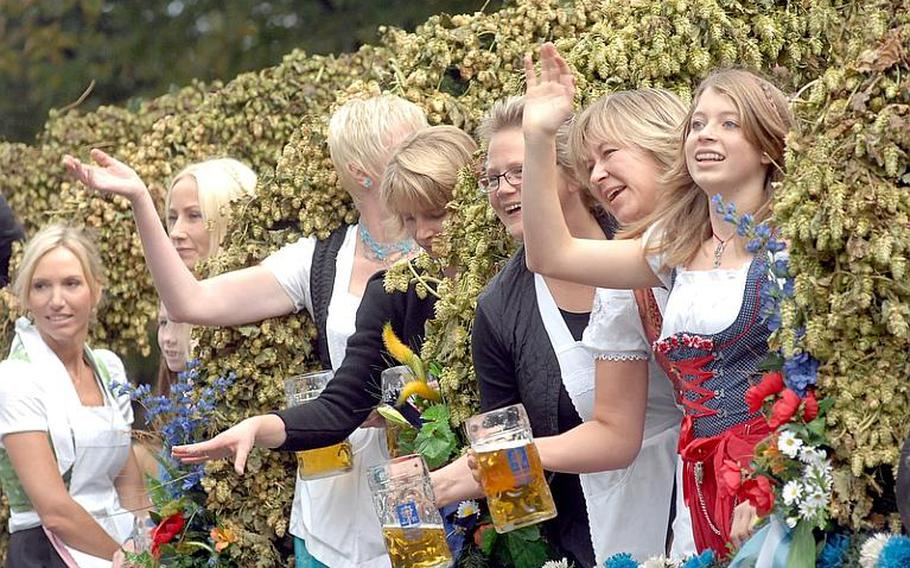 Participants in the parade of Oktoberfest ?landlords? (owners of the beer tents) and breweries wave to spectators on opening day at Oktoberfest in Munich Saturday.