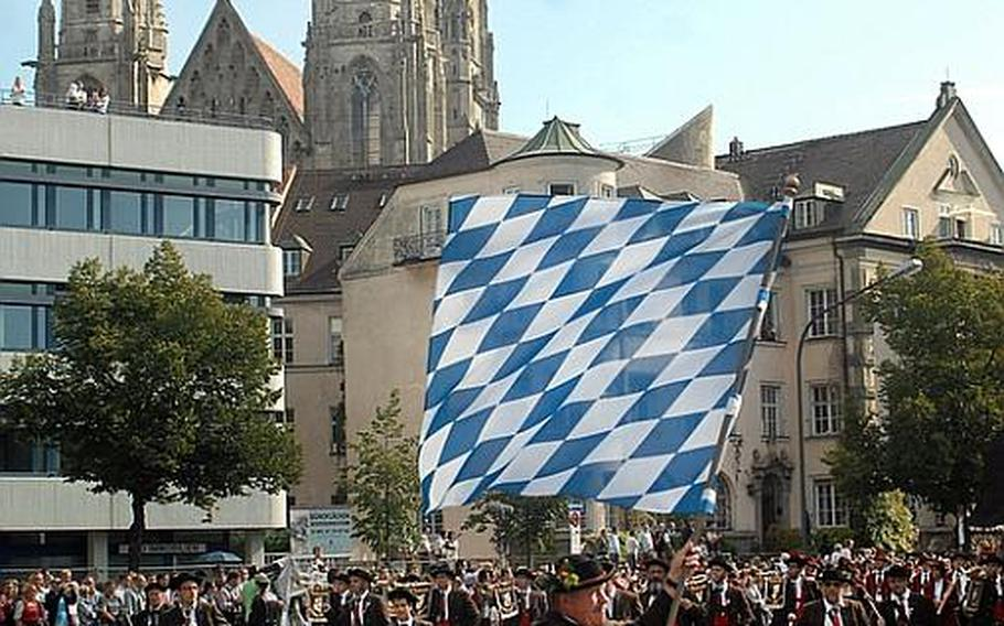 The opening day parade proceeds down the street toward the Oktoberfest grounds in Munich on Saturday, as the annual beer festival opened.
